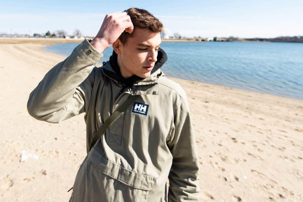 Boy on the beach wearing a winter coat.