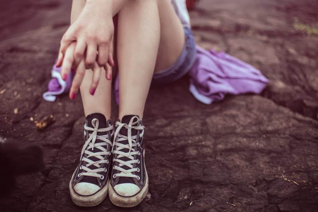 girl sitting on ground with black Converse sneakers