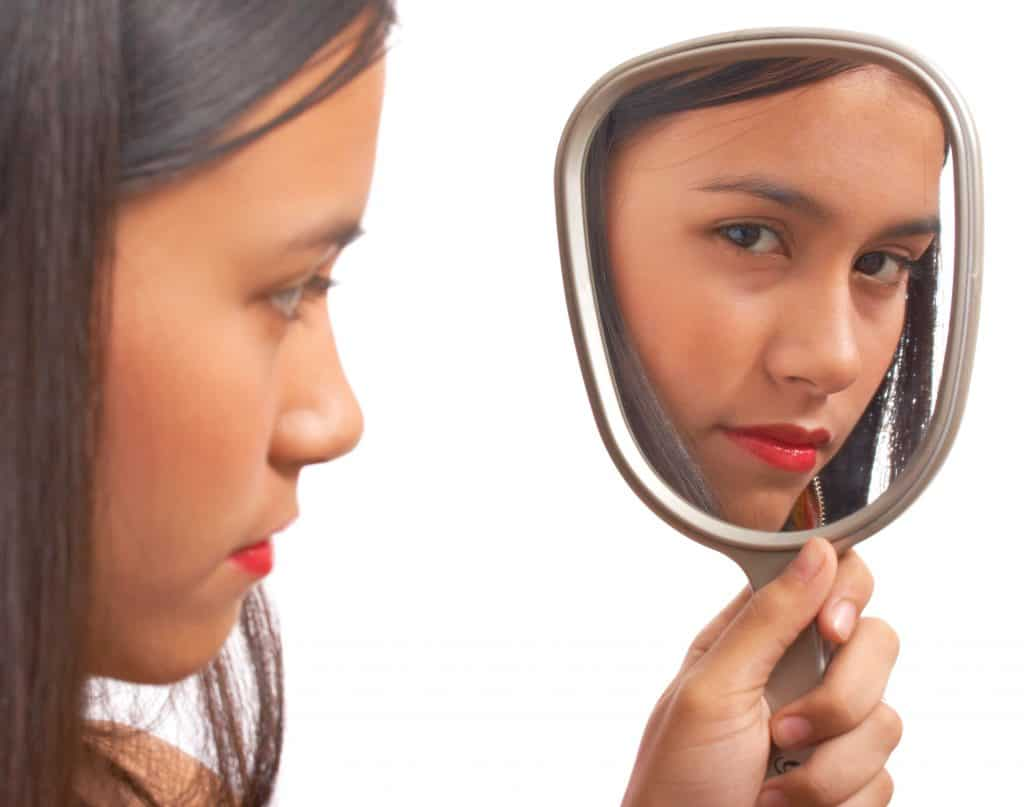 Unhappy Girl Looking At Her Reflection On The Mirror