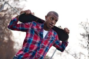 A young man hanging out holding his skateboard on the back of his shoulders over his head.