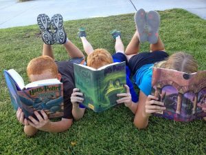 Three children lying on the grass reading Harry Potter Books.