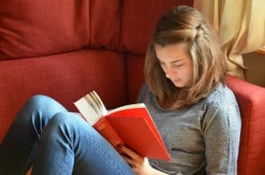 Teen girl in chair reading a book.