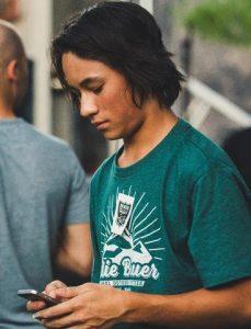 Teen boy looking down at phone.