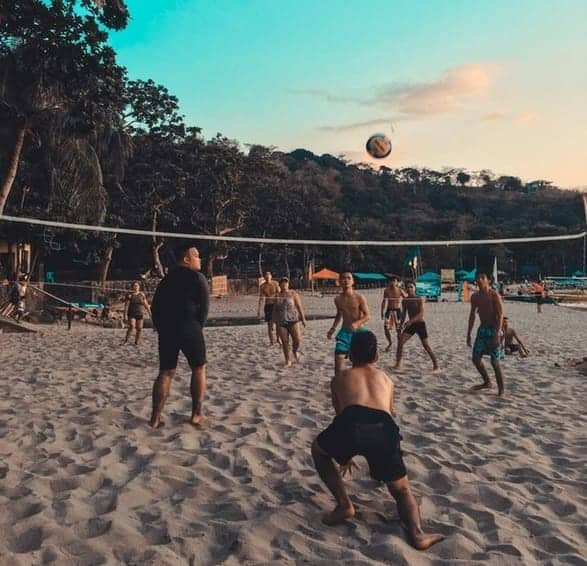 Teens playing volleyball on the beach
